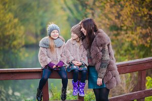 Adorable little girls and young mother in autumn park outdoors