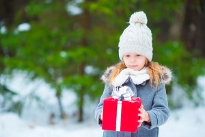 Adorable little girl with christmas box gift in winter day outdoors