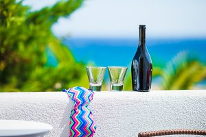 Glasses, bottle of tasty wine and swimsuit on balcony in greek island with view of sea