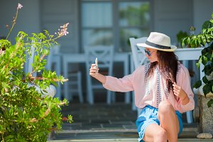 Young beautiful woman taking selfie with phone outdoors during summer vacation
