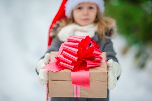 Closeup xmas box in hands of adorable little girl in winter day outdoors