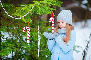 Portrait of a little cute smiling girl in a blue coat and mittens standing near the decorated Christmas tree on a frosty winter day outdoor.