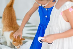 Closeup of Little adorable girls stroking a red cat in greek village, Mykonos, Greece, Europe