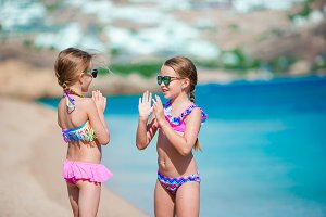 Adorable little girls having fun during beach vacation. Slapping each other on the palms