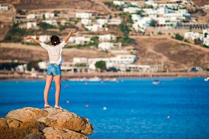 Young happy girl on the edge of a cliff with amazing view of old small village in Mykonos, Greek