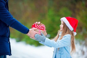 Adorable little girl giving christmas box gift in winter outdoors