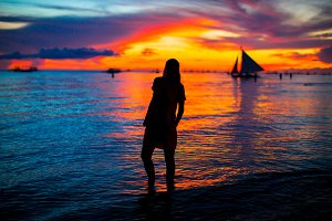 Young woman at tropical beach in beautiful sunset
