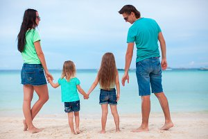 Happy family of four on the beach