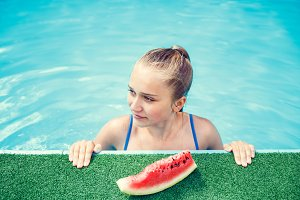 Happy teenage girl relaxing in swimming pool
