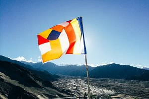 One single Buddhist prayer flag in six colors fluttering in mountain region against the sunlight. - The colorful flags can represent Tibetan culture and Buddhist religion symbol very well