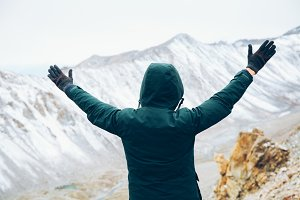 Back of happy and cheerful man in coat standing and raising hands up in snowy mountain scenery - freedom concept