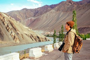 Travel photographer with DSLR camera and big lens in mountain scene, Leh, India