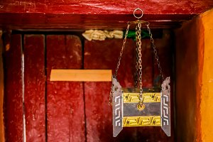 Ancient Tibetan incense tools in Buddhist temple against red wood door