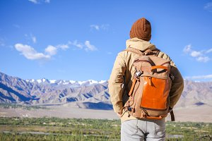 Young male travel backpacker on adventure watching mountains determined to climb and hike