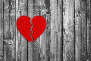 Broken heart on black and white wood