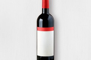 Red wine bottle on white table