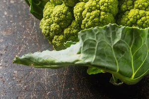 Ripe green cauliflower with leaves. Dark wood background.