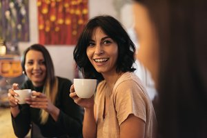 women drinking coffee in cafe bar.