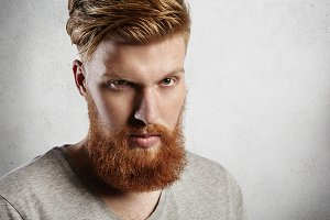 People and lifestyle. Headshot of handsome hipster with thick red beard and stylish hair looking at camera with serious face expression, squinting his eyes. Fashionable student posing in studio