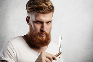 Attractive redhead hipster barber with stylish haircut and thick beard holding cut-throat razor, looking at camera with serious face expression. Caucasian hairdresser with straight razor in his hands