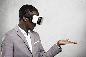 Technology, entertainment, gaming and cyberspace. African office worker in formal suit experiencing virtual reality using 3d headset for mobile phone, looking at his open palm as if holding something