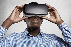 People, technology, cyberspace and entertainment concept. African man dressed in checkered shirt using 3d headset, playing video games. Black man experiencing virtual reality, wearing oculus glasses