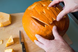 Man cuts pumpkin for Halloween