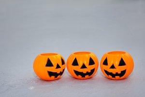 Orange jack-o-lantern bucket pumpkins on grungy background