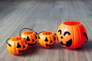 Group of happy and smiling jack-o-Lantern pumpkin buckets on wooden background