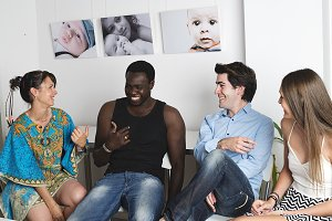 Group of mixed race young people talking and laughing together. Pictures on the wall at background.