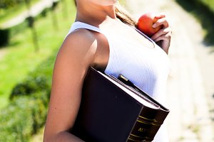 woman with book and red apple