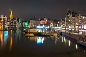 Night panorama of Amsterdam canal Damrak, Holland