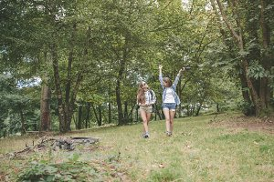 Hiker woman raising arms and enjoying with friend