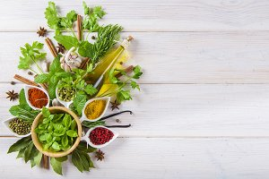 Fresh herbs and spices on a white wooden background