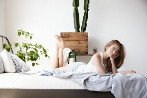 woman in bed in sunny loft