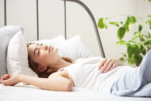 woman in bed in sunny loft