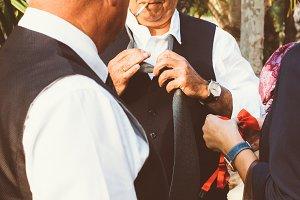 Aged man untying necktie