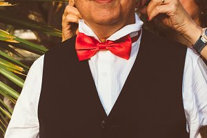 Woman hands helps to put a bow tie