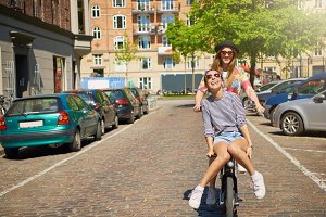 Two young girlfriends having fun on a bicycle