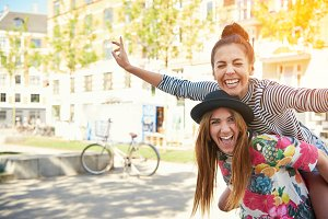Laughing young female friends piggy back riding