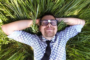man in glasses lying on green
