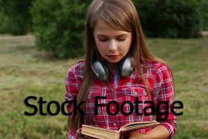 Girl with headphones reading book