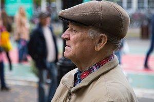 Elderly man in a cap looks