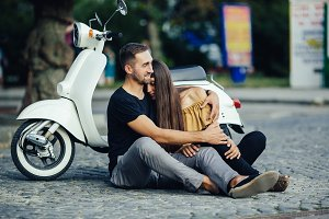 Cute couple with their scooter in the city