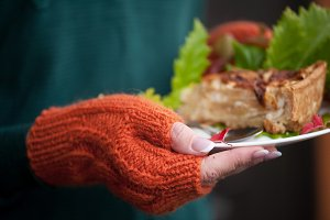 hands in orange mittens hold a plate with cake