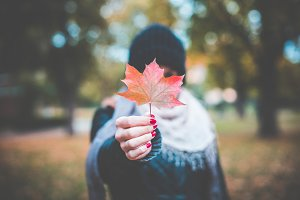 Girl Holding Autumn Colored Leaf
