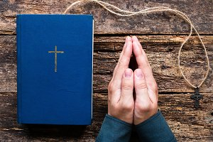 man praying next to the bible