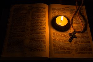 burning candle and a cross on bible