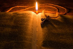 cross on the bible by candlelight