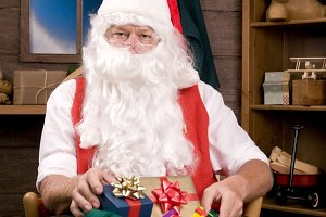 Santa Claus in Workshop With Present